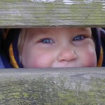 Child hiding behind boards